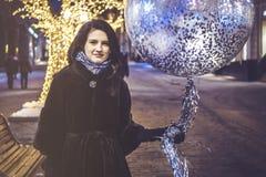 Jeune fille avec le baloon marchant dans les rues de ville de nuit Photos libres de droits