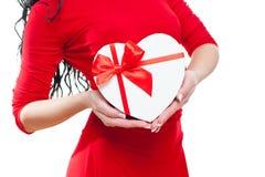 Jeune fille avec le boîte-cadeau en forme de coeur rouge dans une robe rouge sur le fond blanc Photo libre de droits