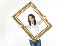 Jeune fille avec le cadre de tableau devant elle Photo stock
