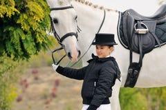 Jeune fille avec le cheval blanc de dressage Photographie stock libre de droits