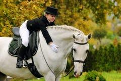 Jeune fille avec le cheval blanc de dressage Photographie stock