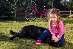 Jeune fille avec le chien jouant dans le jardin Photographie stock libre de droits
