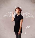 Jeune fille avec le dessin de klaxons et d'ailes de diable Images stock