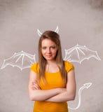 Jeune fille avec le dessin de klaxons et d'ailes de diable Image libre de droits