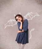 Jeune fille avec le dessin de klaxons et d'ailes de diable Photographie stock libre de droits