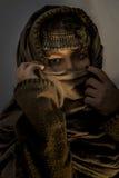 Jeune fille avec le foulard, le capot et les bijoux sur sa tête Photo stock