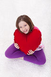 Jeune fille avec le grand oreiller rouge de coeur Photos stock