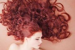 Jeune fille avec le long cheveu se trouvant sur l'étage image libre de droits