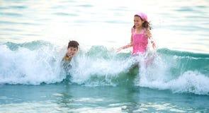 Jeune fille avec le petit frère appréciant le grand wa Photos stock