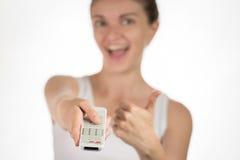 Jeune fille avec le pressing à télécommande sur des boutons, souriant et Image stock