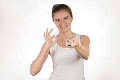 Jeune fille avec le pressing à télécommande sur des boutons, souriant et Images stock