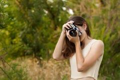 Jeune fille avec le rétro appareil-photo de photo Photos stock
