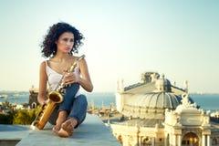 Jeune fille avec le saxophone sur le parapet de toit photographie stock