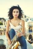 Jeune fille avec le saxophone sur le parapet de toit photos libres de droits