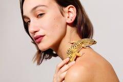 Jeune fille avec les épaules nues sur un fond gris Un gecko d'iguane rampe au-dessus de ses épaules inside photos stock