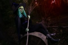 Jeune fille avec les cheveux et le balai verts dans le costume de la sorcière dans le temps de Halloween de forêt Photos stock