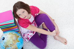 Jeune fille avec les livres d'école et le globe de la terre Photographie stock libre de droits
