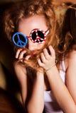 Jeune fille avec les lunettes de soleil de port de cheveux bouclés avec l'Américain Photo stock