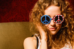 Jeune fille avec les lunettes de soleil de port de cheveux bouclés avec l'Américain Photo libre de droits