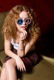 Jeune fille avec les lunettes de soleil de port de cheveux bouclés avec l'Américain Photos stock