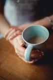 Jeune fille avec les mains intéressantes avec la manucure française blanche tenant une tasse de vintage de café bleue Photos libres de droits