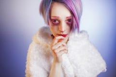Jeune fille avec les yeux et les cheveux roses, comme une poupée Photographie stock libre de droits