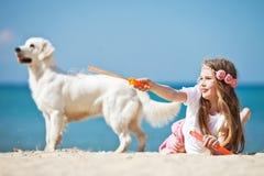 Jeune fille avec son chien par le bord de la mer Image stock