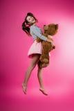 Jeune fille avec un jouet de peluche image stock