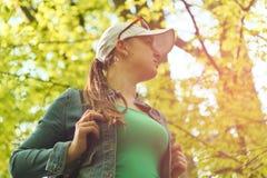 Jeune fille avec un sac à dos sur un fond d'arbre Image libre de droits