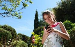Jeune fille avec un téléphone portable Photos stock
