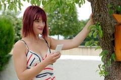 Jeune fille avec un téléphone portable en parc, dehors Photographie stock libre de droits