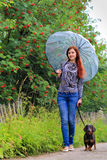 Jeune fille avec un teckel un jour pluvieux Photographie stock libre de droits