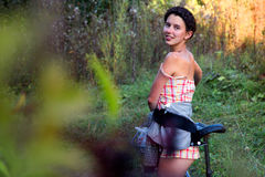 Jeune fille avec un vélo sur un chemin forestier Photographie stock