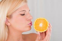 Jeune fille avec une orange blanche Images libres de droits