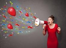 Jeune fille ayant l'amusement, criant dans le mégaphone avec des ballons Photographie stock libre de droits