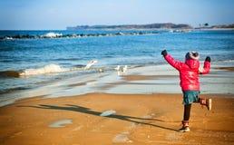 Jeune fille ayant l'amusement sur la plage de Baltique d'hiver Photographie stock