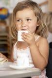 Jeune fille ayant le thé à Montessori/à école maternelle Photographie stock libre de droits