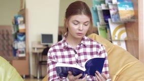 Jeune fille blanche d'université lisant un livre pour trouver des informations banque de vidéos
