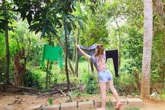 Jeune fille blanche traînant les vêtements pour sécher après lavage photos stock