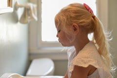 Jeune fille blonde à l'évier de salle de bains pendant le matin photographie stock libre de droits