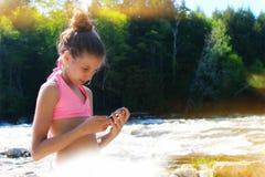 Jeune fille blonde à l'aide du smartphone dehors Photos libres de droits