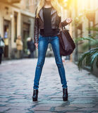 Jeune fille blonde à la mode avec de longues jambes utilisant des blues-jean, manteau brun en cuir et tenant un sac marchant et f images stock