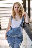 Jeune fille blonde élégante dans des combinaisons de denim dehors avec la lumière du jour naturelle, un jour ensoleillé Photographie stock libre de droits