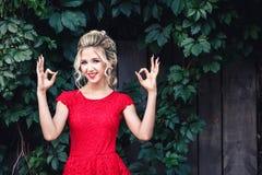 Jeune fille blonde attirante dans la robe rouge posant près d'un vignoble sauvage et montrant le signe d'ok image libre de droits