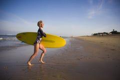 Jeune fille blonde attirante et heureuse de surfer en belle plage portant le panneau de ressac jaune sortant en courant de la mer image libre de droits