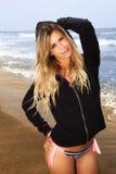 Jeune fille blonde avec du charme et douce à la mer se tenant avec le pull molletonné noir images stock