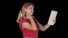 Jeune fille blonde avec le comprimé à disposition, faisant un appel visuel ou enregistrant la vidéo, souriant, Alpha Channel banque de vidéos