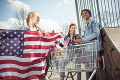 Jeune fille blonde avec le drapeau américain tenant les amis proches ayant l'amusement Photo libre de droits