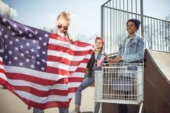 Jeune fille blonde avec le drapeau américain tenant les amis proches ayant l'amusement Images libres de droits