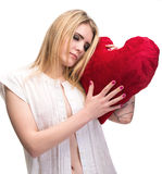 Jeune fille blonde avec un oreiller de coeur Photographie stock